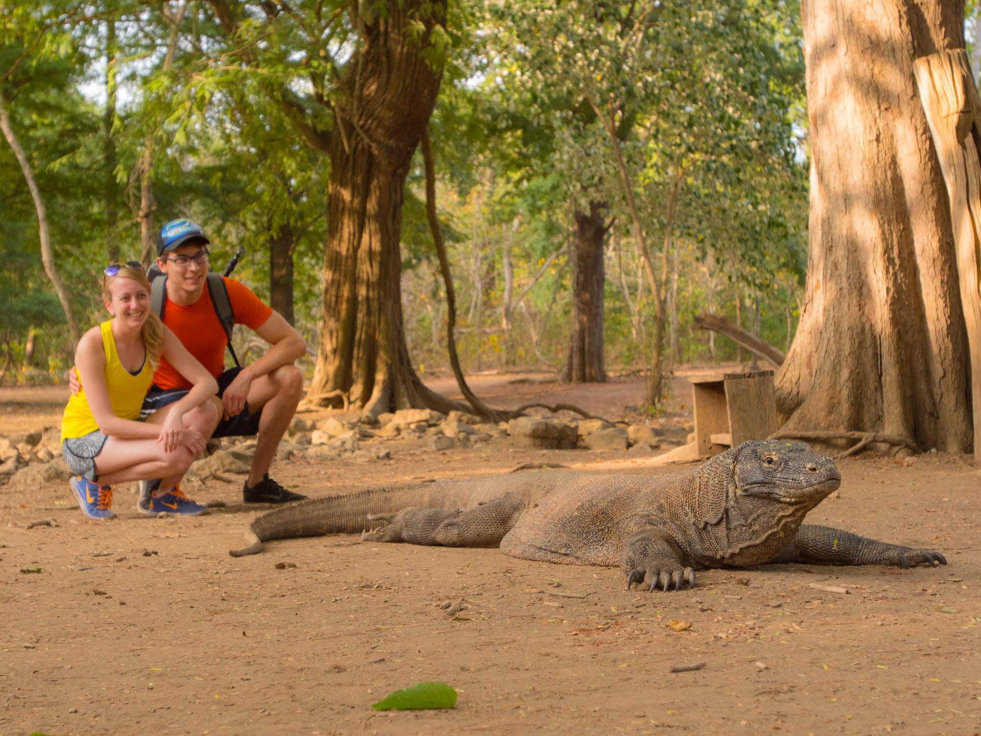 two people posing behind Komodo dragon