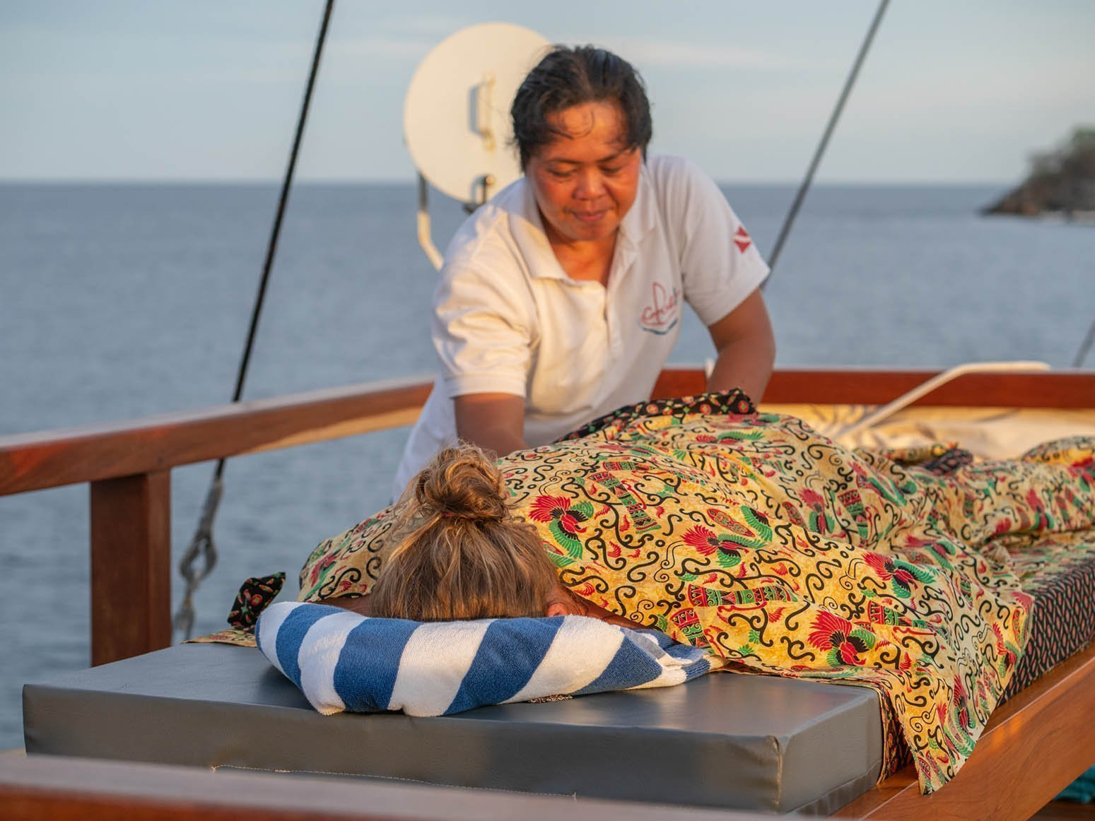 guest recieving massage from liveaboard staff